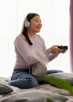 ベッドでビデオゲームをしている幸せな女の子