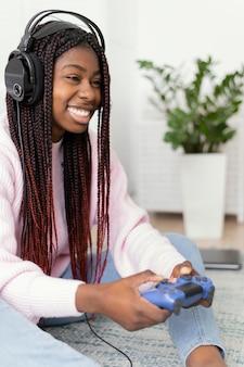 Счастливая девушка играет в видеоигры дома