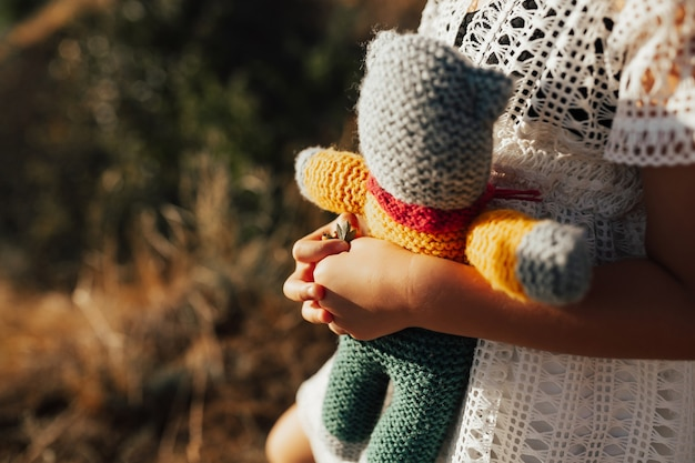 夏の間に自然の中でニットのおもちゃで遊ぶ幸せな女の子