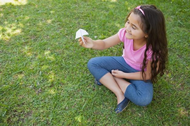 公園で紙飛行機で遊んでいる幸せな女の子
