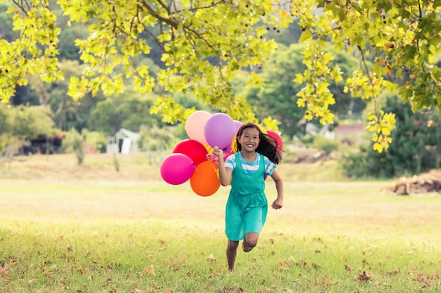 Happy girl playing with balloons in park