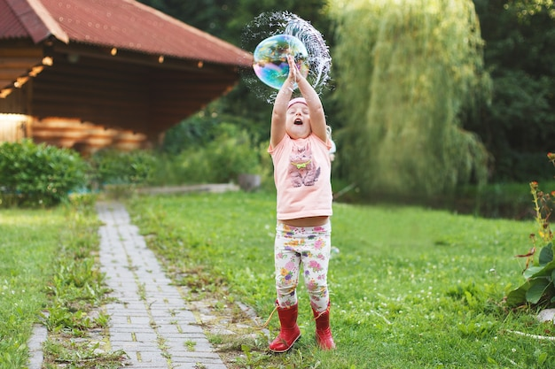 Happy  girl playing with soap bubbles outdoor little girl pops a soap bubble