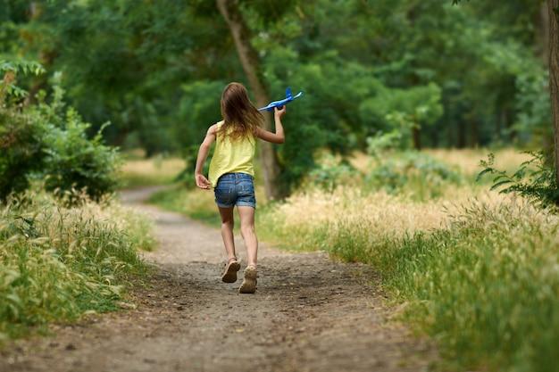 屋外でおもちゃの飛行機で遊ぶ幸せな女の子