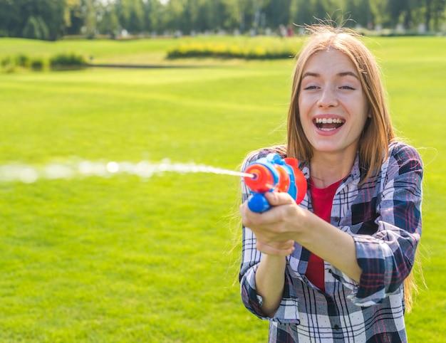 Счастливая девушка играет с водяной пушкой
