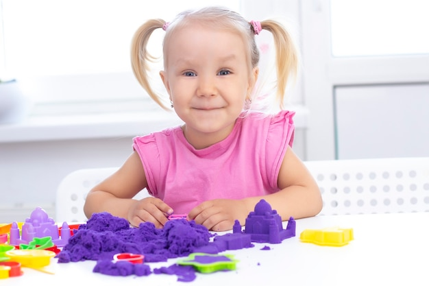 Happy girl plays kinetic sand in quarantine. blond beautiful girl smiles and plays with purple sand on a white table.