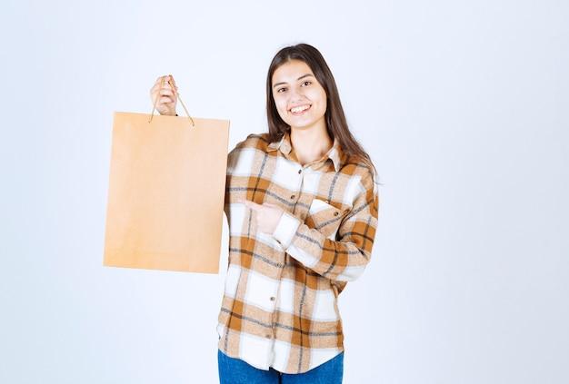 흰 벽 위에 종이 공예 패키지를 가리키는 행복한 소녀.