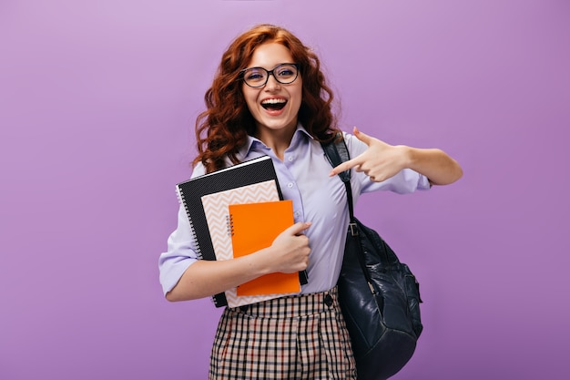 Happy girl pointing to notebooks on purple wall Premium Photo