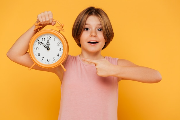 Happy girl pointing with finger at alarm clock isolated