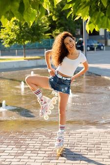 Счастливая девушка позирует в роликовых коньках рядом с фонтаном