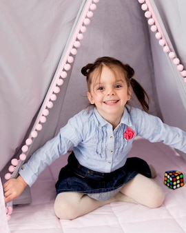 Happy girl posing in tent at home