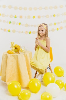 レモネードガラスを押しながらポーズをとって幸せな女の子