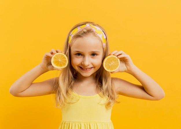 Счастливая девушка позирует с ломтиками лимона