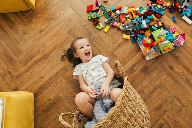 Happy girl poured blocks on the floor and lies in a basket and laughs. playtime and mess in kid's room