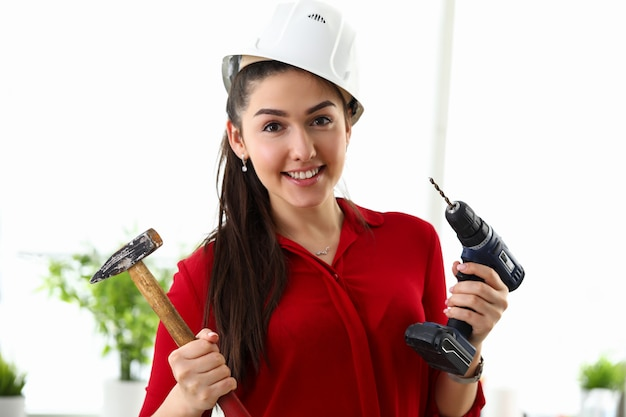 Happy girl protective helmet holds drill and hammer
