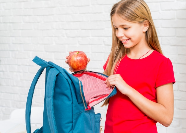 Happy girl putting apple in backpack