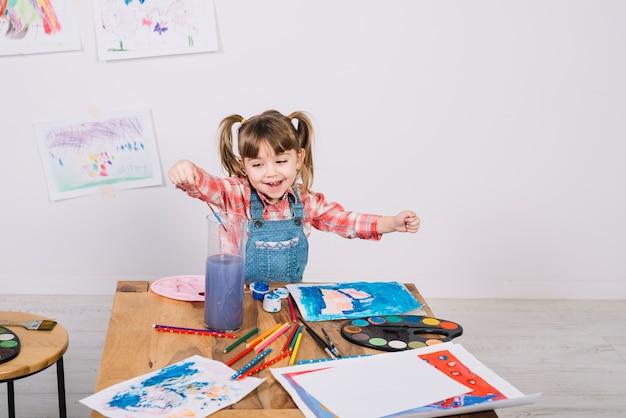 Happy girl putting paint brush into muddy water