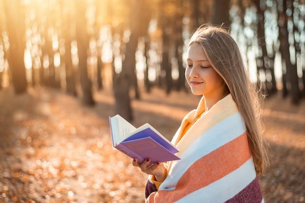 가을 공원에서 책을 읽는 행복한 소녀