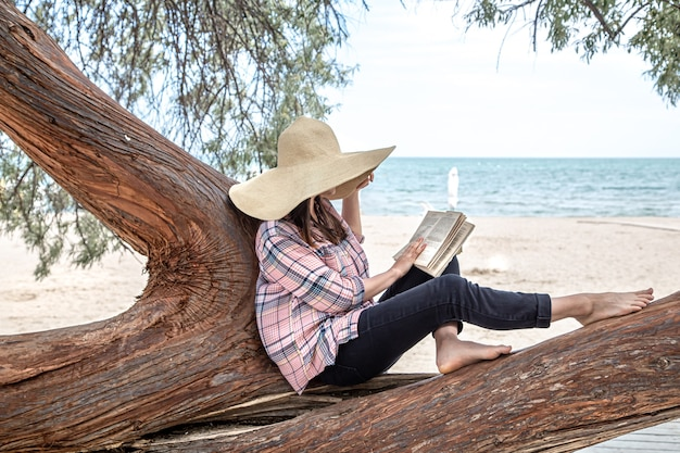 A happy girl reads a book on a tree. the person abstracted from everything. the concept of relaxation and tranquility.
