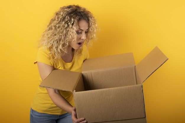 幸せな女の子は、オンラインショップの注文からパッケージを受け取ります。黄色の壁。