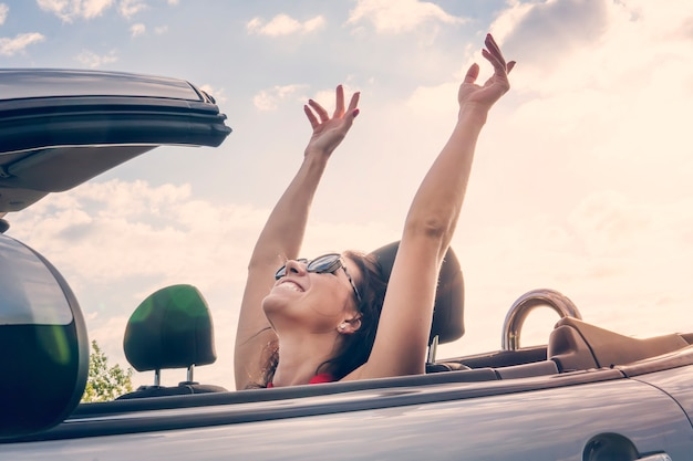 旅行で離れて運転している夏の遠征休暇でコンバーチブル車に座って太陽の光を楽しんでリラックスして幸せな女の子。自由を感じている自由の概念の女性は彼の手を上に上げた。風に乗って。