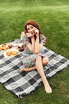 Счастливая девушка, отдыхая на природе. молодая рыжеволосая девушка в платье сидит на одеяле, держа в руках тарелку с клубникой. еда для пикника лежит на покрывале. летний отдых. гулять в парке.