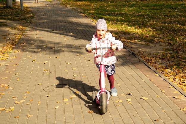 幸せな女の子は秋に公園の小道でスクーターに乗る。
