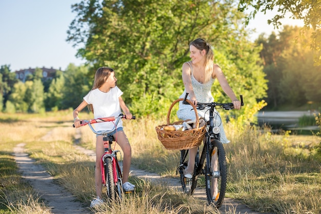 Happy girl riding on bicycle with her mother in meadow at sunset