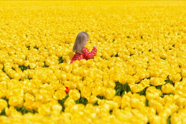 노란 튤립 밭에서 달리는 행복한 소녀