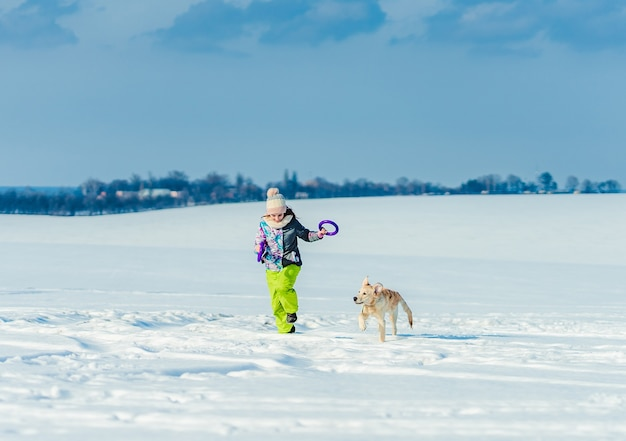 輝く雪の中でかわいい犬と一緒に走っている幸せな女の子