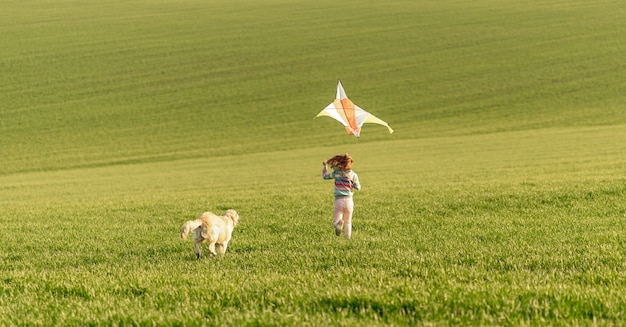 Happy girl running with kite