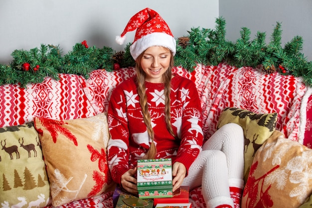 Happy girl in santa claus hat opens a christmas gift box with present inside