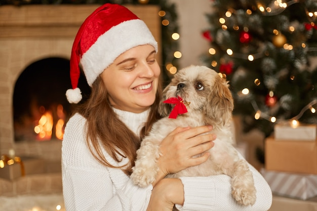 Happy girl in santa hat and white sweater hugging with cute pekingese dog by a christmas tree with lights and fireplace in festive room, female looking at pet with toothy smile.