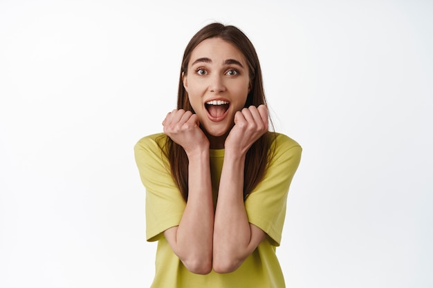 행복한 소녀는 비명을 지르며 기뻐하며 흰색에 서 있는 멋진 큰 뉴스를 확인합니다.