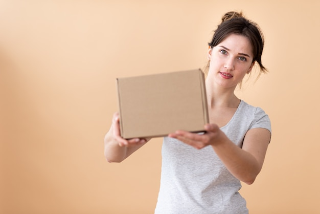 Happy girl showing craft box in her hands and smiling joyfully in the space. box in focus with free space for text.