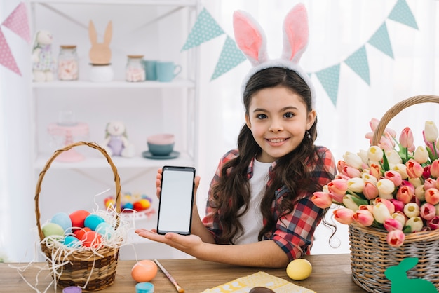 Happy girl showing mobile phone with easter eggs and tulips basket on table
