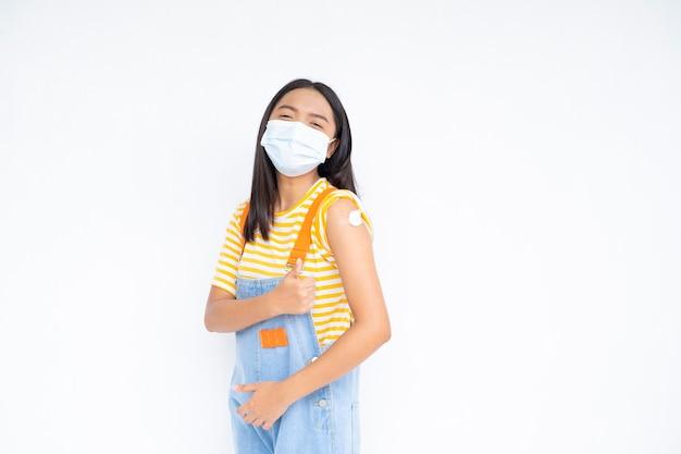 白い背景の上のワクチン接種後の肩を示す幸せな女の子。