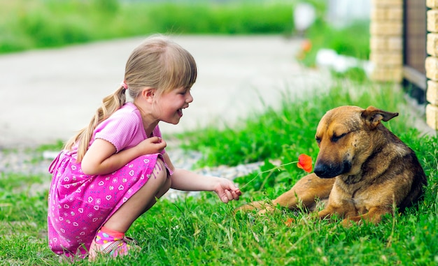 Happy girl shows flower to a dog