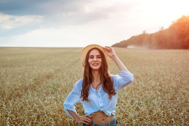 행복 한 소녀 밀짚 모자에 밀밭에 앉아 캐주얼 옷을 입고 백인 민족성의 귀여운 젊은 여자.