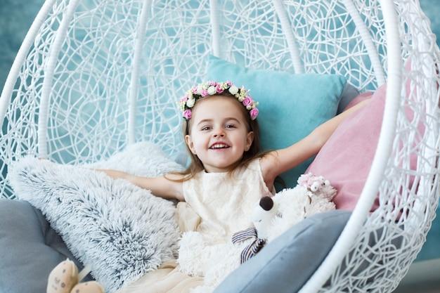 Счастливая девочка сидит в белом висячем кресле и разводит руками