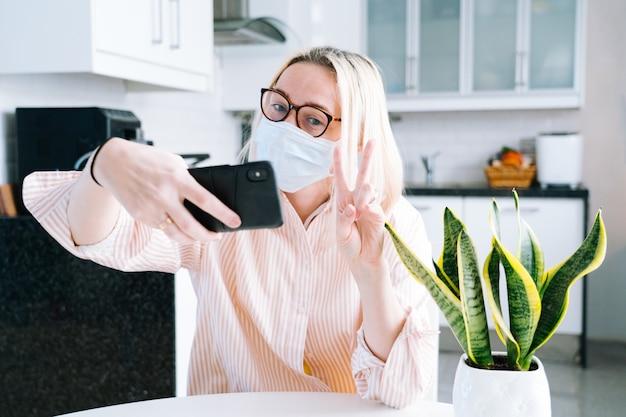 Счастливая девушка сидя дома кухня и держа видеозвонок. молодая женщина, используя смартфон для видео-звонка с другом или семьей. запись на вебинар vlogger. женщина смотрит в камеру и машет руками приветствия