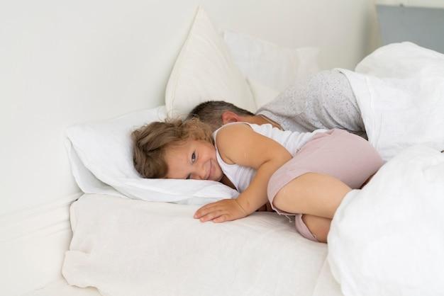 彼女の父親と一緒にベッドに座っている幸せな女の子