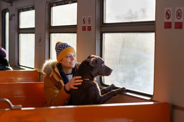 Happy girl sitting in local train with her dog, hugging, looking through the window in winter time.