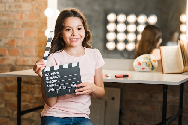 Happy girl sitting in makeup room holding clapper board