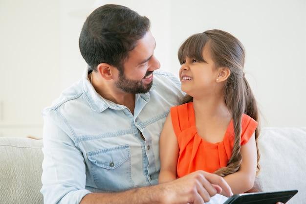 彼女のお父さんの膝の上に座って、笑って幸せな女の子。父はタブレットを押しながら娘との時間を楽しんでいます。