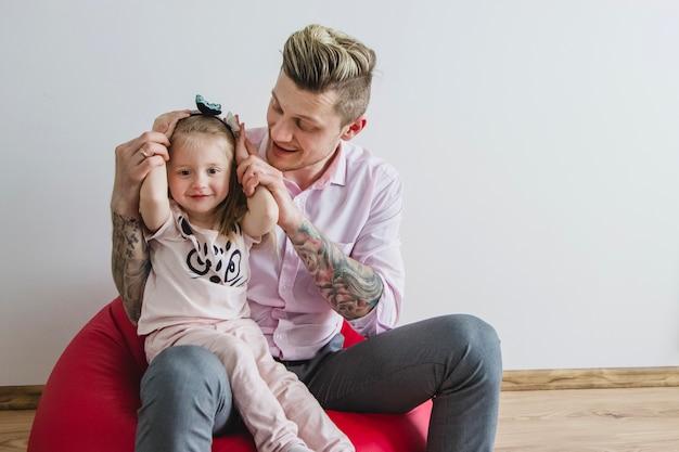 父親の脚に座っている幸せな女の子