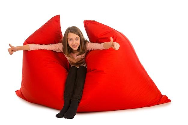 リビングルームまたは白で隔離された他の部屋の赤いお手玉ソファに座っている幸せな女の子
