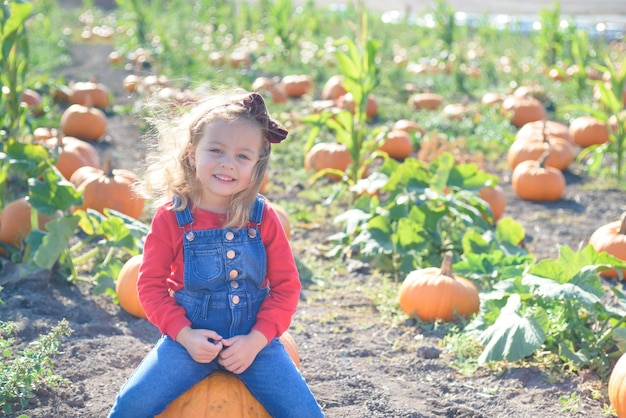 Happy girl sitting on pumpkin at farm field patch