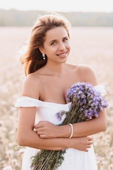 필드에 꽃의 꽃다발과 함께 흰 드레스에 행복 소녀 미소