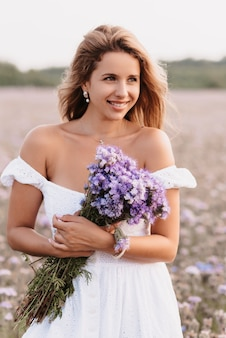 Happy girl smiles in a white dress with a bouquet of flowers in the field