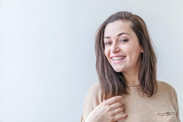 Счастливая девушка улыбается. женщина брюнет портрета красоты молодая счастливая положительная изолированная на белой предпосылке.